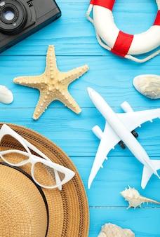 Самолет с аксессуарами путешественника на синем фоне. концепция путешествия. вертикальное фото