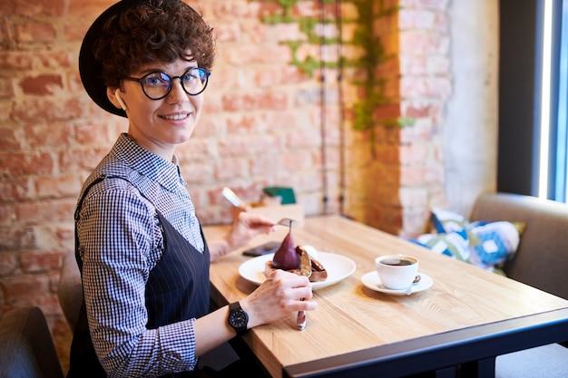 Счастливая молодая женщина с airpods в ушах, глядя на вас, сидя в кафе и вкусный десерт