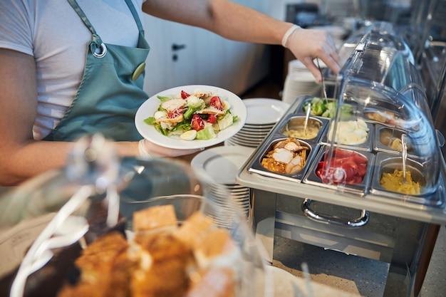 空港のカフェの従業員がプレートに食べ物を追加する
