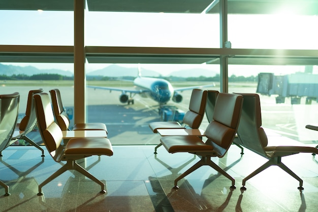 Airport departure lounge seating with aircraft preparing for flight in the background