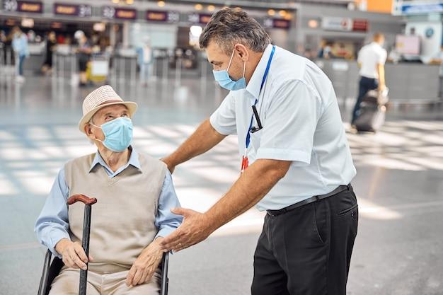 휠체어에 앉아 걷는 지팡이로 수석 관광객에게 이야기하는 공항 직원