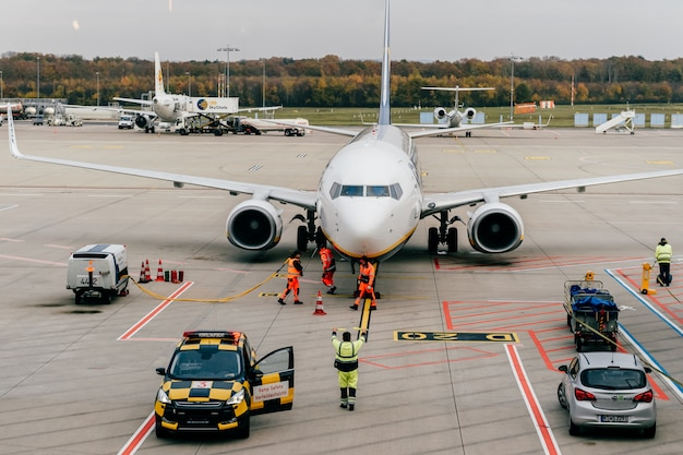 Airport employees  service landed airplane. view from waiting room through window at runway with aircraft and maintenance staff in work flow