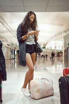 彼女の飛行のためにターミナルで待っているゲートで空港の女性の乗客。オンラインチェックイン、空の旅