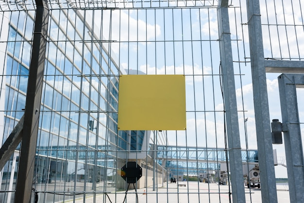 Airport fence grille on the background of passenger bridges for boarding passengers. place for the test on the plate.