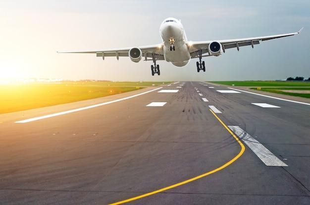 朝の夜明けに太陽のまぶしさでゴムタイヤの痕跡がある空港の滑走路飛行機。