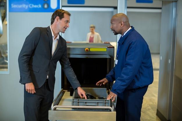 Сотрудник службы безопасности аэропорта взаимодействует с пассажирами при проверке пакета