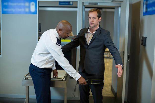 Сотрудник службы безопасности аэропорта использует ручной металлоискатель для проверки пассажира