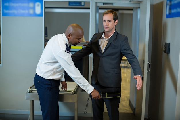 Addetto alla sicurezza aeroportuale utilizzando un metal detector portatile per controllare un pendolare