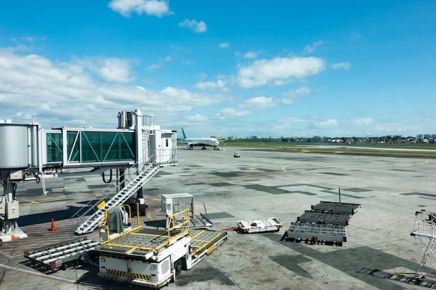 낮에 공항 터미널 야외보기, 건물 외부 다리 도착 비행기 도착 하 고 주차 대기 비행기를 다리.