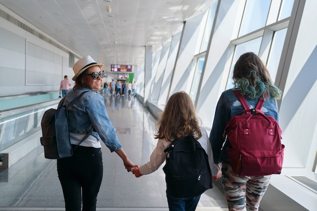 Airport terminal with walking passengers with luggage