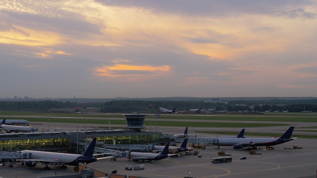 Airport view with airplanes boarding and taking off
