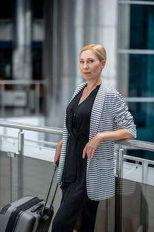 Аэропорт, ожидание. довольно уверенная деловая женщина средних лет с чемоданом стоит в аэропорту в позитивном настроении