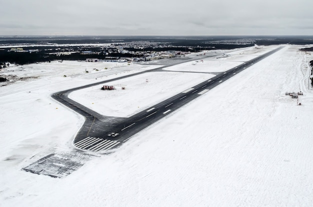 Airport and winter runway, view from a height to a snow-covered landscape.