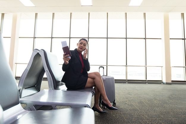 Airport woman on smart phone at gate waiting airport