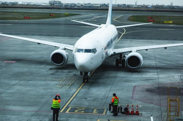 Работник аэропорта у припаркованного самолета