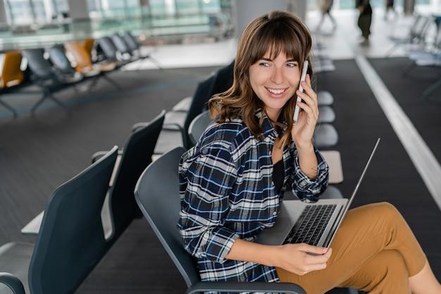 彼女の飛行を待っている間ターミナルホールに座っているスマートフォンとラップトップを持つ空港若い女性の乗客