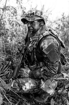 Giocatore di gioco militare di airsoft in uniforme mimetica con fucile d'assalto armato.