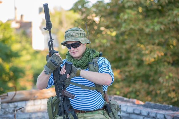 Airsoft player reloads his weapon during a firefight