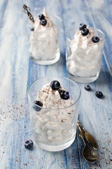 ライトブルーの木製のグラスにブルーベリーとチョコレートのパン粉を添えた風通しの良いデザート