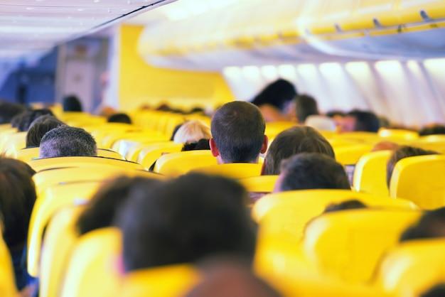 Проход в самолете. интерьер с пассажирами на сиденьях
