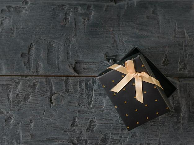 Приоткрытая черная подарочная коробка с бантом на деревянном столе.