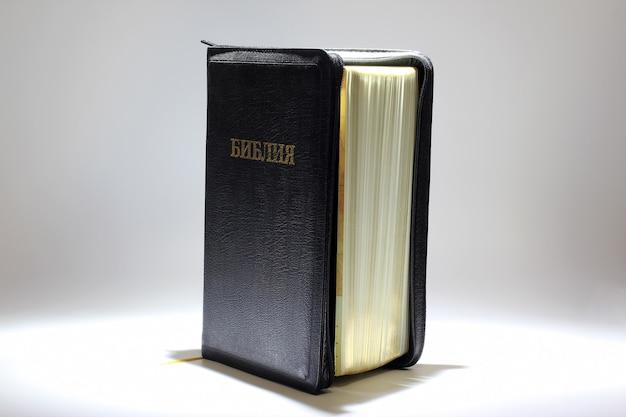 Ajarは白い背景の上に聖書を立てます