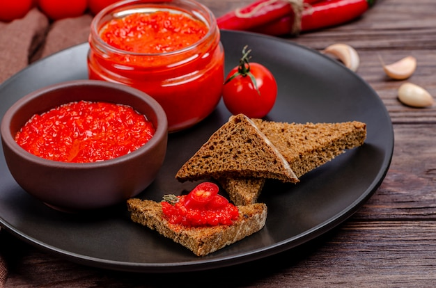 Ajvar or pindjur red vegetable spread and tomato mousse in a clay bowl and glass jar in a black plate on a rustic wooden table