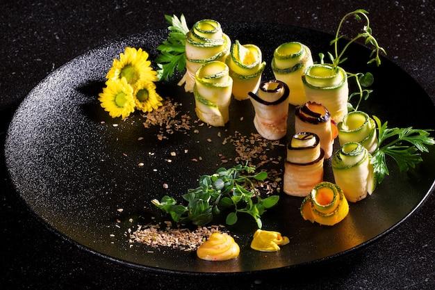 Ajvar zucchini rolls from thegrillは暗い背景の黒いプレートで提供されます。メニューとデザインコンセプト。