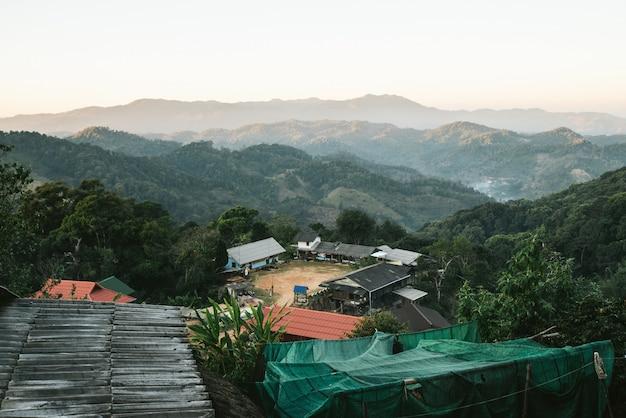 Деревня между слоями горы с солнечным светом и туманом в вечере тот взгляд от деревни akha maejantai на холме в чиангмае, таиланде.