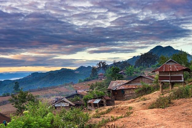 北ラオスの山々に沈む夕日の劇的な空のアカ族の村