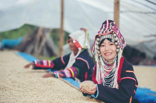 Akhaの女性は微笑んでコーヒーを賞賛しました