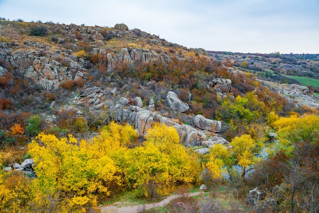 Aktovsky canyon and autumn trees and large stone boulders around
