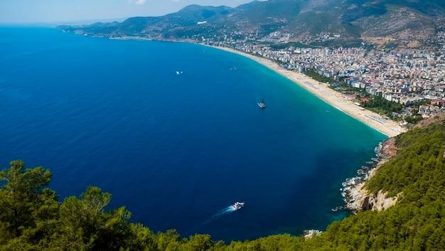 青い海と港都市背景-美しいクレオパトラビーチアラニヤトルコ風景旅行のランドマークの海岸フェリーボートと山のアラニヤビーチトップビュー