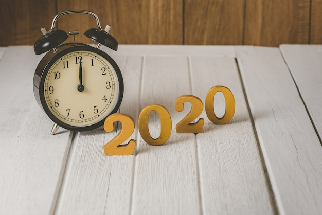 Alarm clock 2020 wooden gold number.  happy new year on nature concept