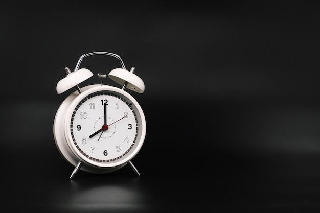 Alarm clock at 8.00 am on black background