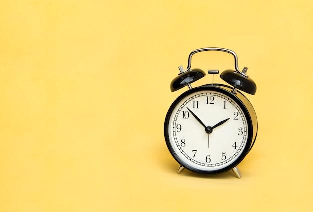 Alarm clock analog classic vintage black on pale yellow background.