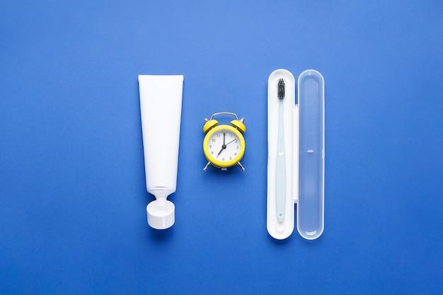 Будильник и зубная щетка в футляре на синем