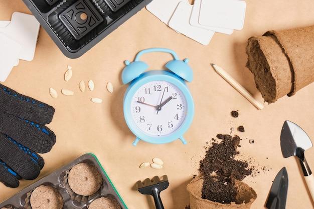 クラフト紙のコピースペースの上面図の目覚まし時計とガーデンツール、小さなヘラプレートの手袋と泥炭の錠剤、苗を植えるためのすべて