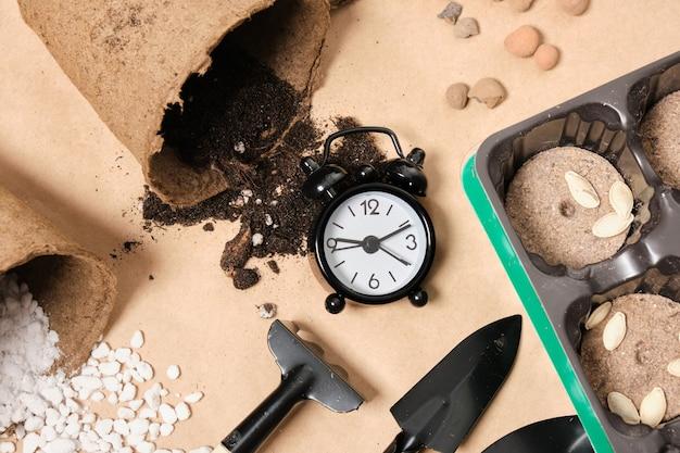 クラフト紙の目覚まし時計とガーデニングツールは、春の苗のコンセプトのトップビュー時間をコピーします