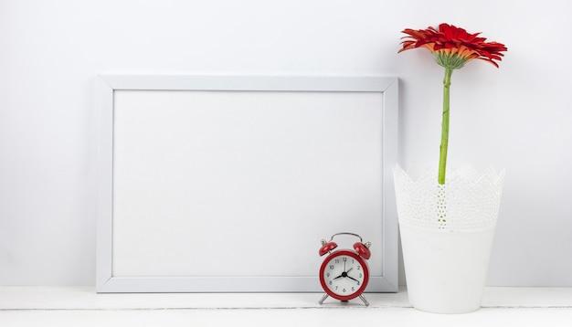 机の上の空のフレームと目覚まし時計とガーベラの花