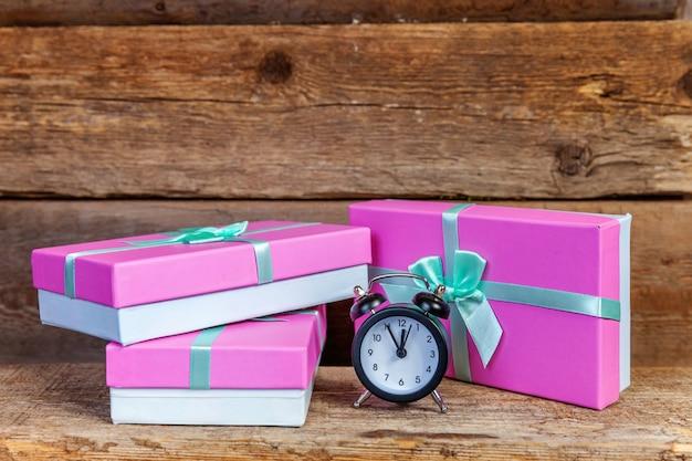 Будильник и подарочная коробка, завернутые в розовую бумагу на старом деревянном фоне