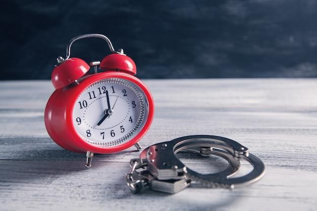 Будильник и наручники на столе