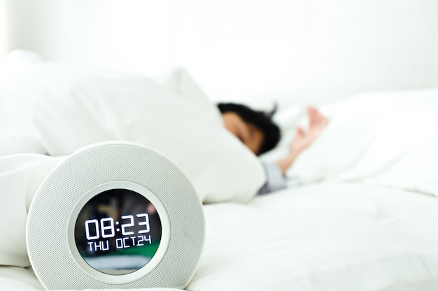 目覚まし時計と寝室で寝ている少年
