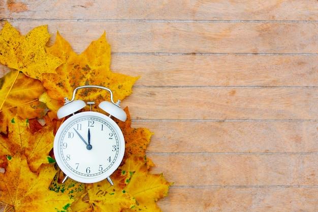木製のテーブルに目覚まし時計とカエデの葉