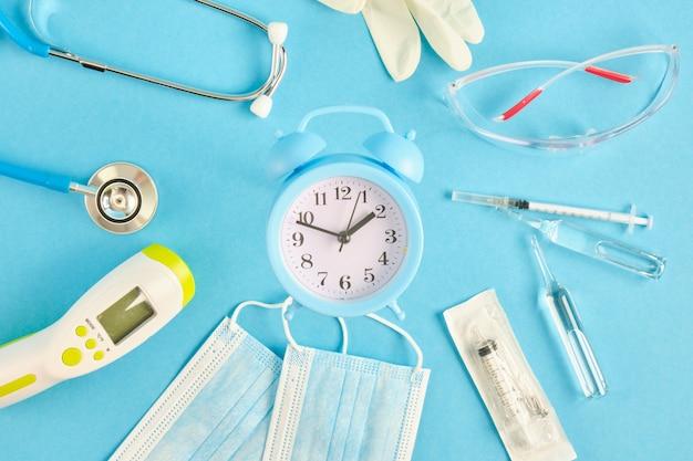 알람 시계 및 의료 장비 파란색 배경 장소 복사 상위 뷰 청진기 비접촉 온도계 앰플 얼굴 마스크 주사기 안전 안경 및 장갑