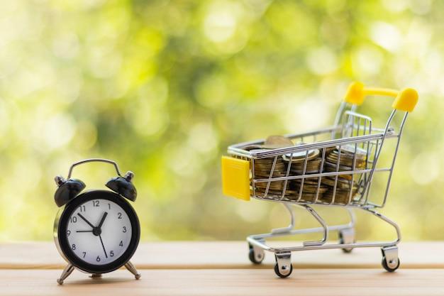 알람 시계와 나무 테이블에 동전이 가득한 미니 쇼핑 카트