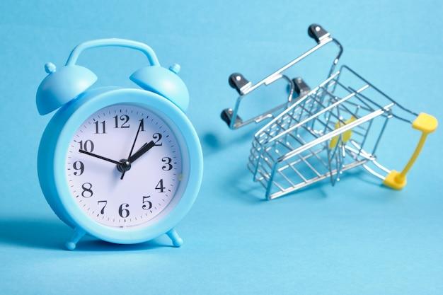 파란색 배경 복사 공간에 알람 시계와 소형 쇼핑 트롤리