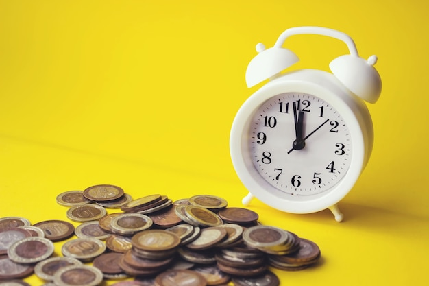 노란색 배경, 금융 개념, 사업 배경에 알람 시계와 돈 동전