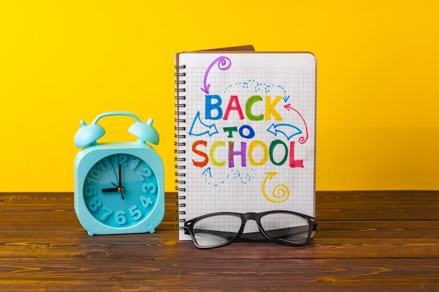 Будильник и блокнот на столе. обратно в школу