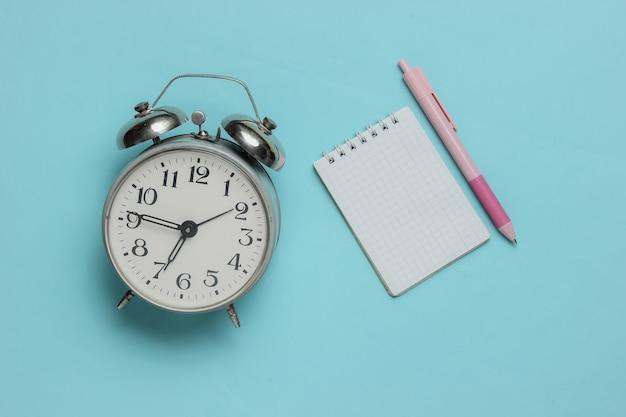 ノートのクローズアップと目覚まし時計とピンクのペン
